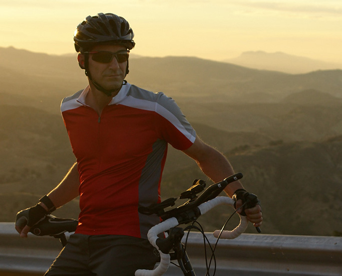 man sitting on a road bike in front of a landscape